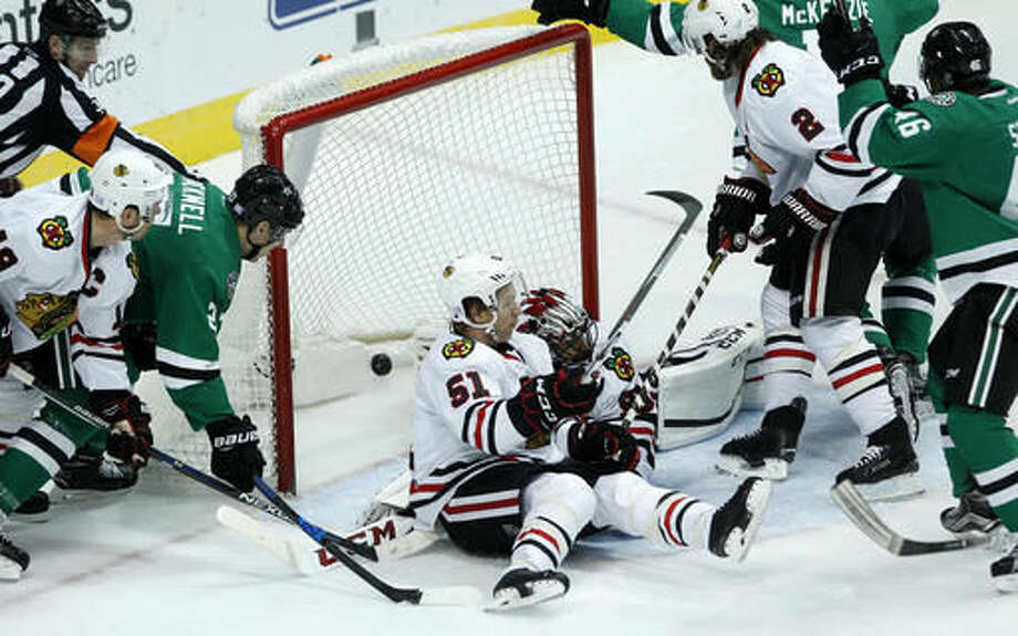 The puck shot by Dallas Stars left wing Curtis McKenzie (11) slips by Chicago Blackhawks goalie Corey Crawford (50) and defenseman Brian Campbell (51) for a goal during the first period of an NHL hockey game Saturday, Nov. 5, 2016, in Dallas. (AP Photo/Tim Sharp)