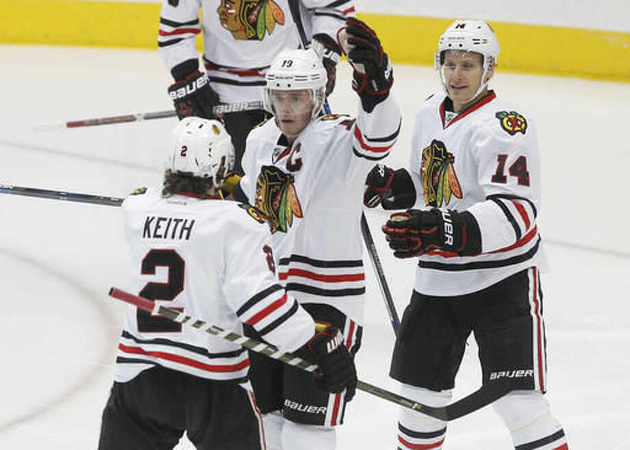 Chicago Blackhawks center Jonathan Toews (19) is congratulated by defenseman Duncan Keith (2) and left wing Richard Panik (14) after scoring a goal against Dallas Stars goalie Antti Niemi during the first period of an NHL hockey game Saturday, Nov. 5, 2016, in Dallas. (AP Photo/Tim Sharp)