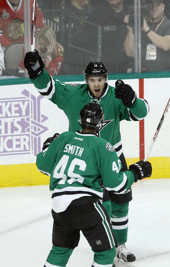 Dallas Stars left wing Curtis McKenzie celebrates with center Gemel Smith (46) after scoring a goal against Chicago Blackhawks goalie Corey Crawford during the first period of an NHL hockey game Saturday, Nov. 5, 2016, in Dallas. (AP Photo/Tim Sharp)