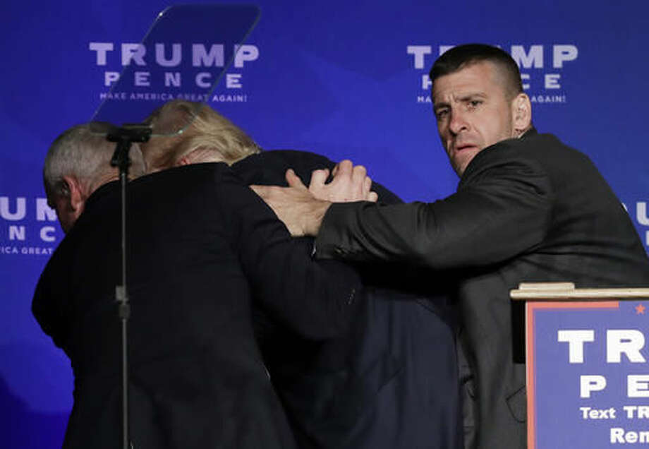 Secret Service agents rush Republican presidential candidate Donald Trump off the stage during a campaign rally in Reno, Nev., on Saturday, Nov. 5, 2016. He returned to the podium afterwards. (AP Photo/John Locher)