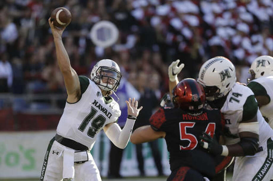 Hawaii quarterback Dru Brown, left, throws a pass during the first half of an NCAA college football game against San Diego State on Saturday, Nov. 5, 2016, in San Diego. (AP Photo/Gregory Bull)