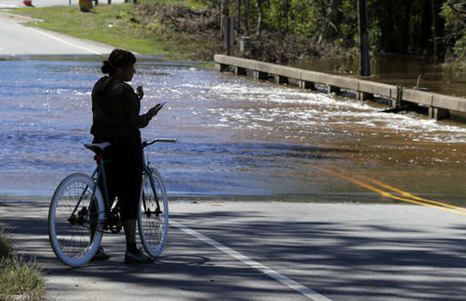 A woman watches floodwaters from Hurricane Matthew rush over a bridge in Spring Lake, N.C., Sunday, Oct. 9, 2016. Hurricane Matthew's torrential rains triggered severe flooding in North Carolina on Sunday as the deteriorating storm made its exit to the sea, and thousands of people had to be rescued from their homes and cars. (AP Photo/Chuck Burton)