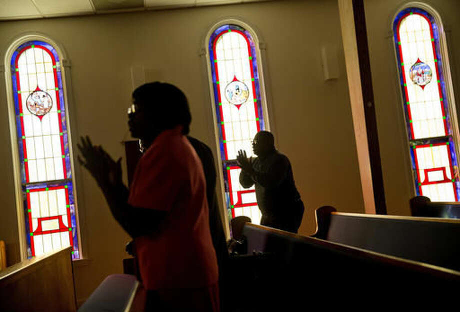 Arthur Green, right, sings along during a service at Mount Horr A.M.E. Church after Hurricane Matthew knocked out power in Hollywood, S.C., Sunday, Oct. 9, 2016. A deteriorating Matthew was stripped of hurricane status Sunday morning and began making its slow exit to the sea. (AP Photo/David Goldman)