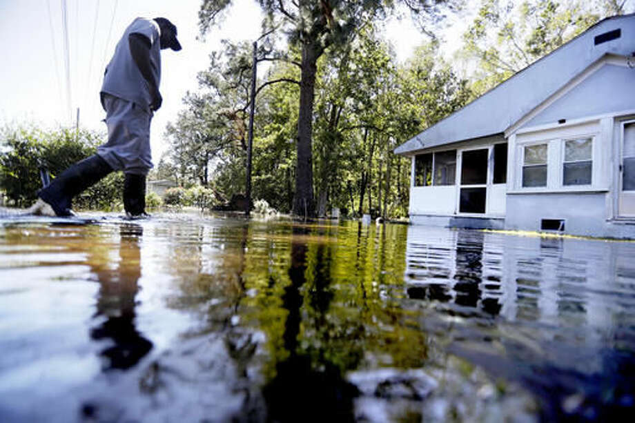 Kyle Simmons wades through water to check on the home of his grandmother following Hurricane Matthew in Edisto Island, Ga., Sunday, Oct. 9, 2016. A deteriorating Matthew was stripped of hurricane status Sunday morning and began making its slow exit to the sea. (AP Photo/David Goldman)