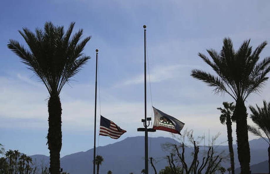 Flags fly at half-staff over John F. Kennedy Memorial Hospital in Indio, Calif., to honor police officers killed in nearby Palm Springs, Sunday, Oct. 9, 2016. The Palm Springs officers trying to resolve a family dispute were killed Saturday when a man they had been speaking with suddenly pulled out a gun and opened fire on them. A third officer was wounded and remained hospitalized.(AP Photo/Reed Saxon)