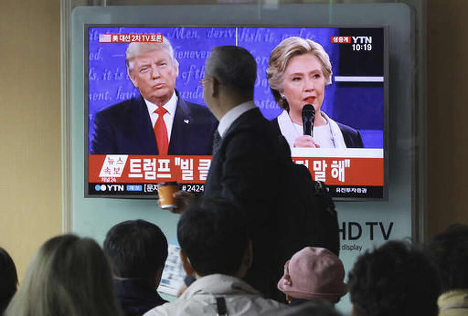 People watch a TV screen showing the live broadcast of the U.S. presidential debate between Democratic presidential nominee Hillary Clinton and Republican presidential nominee Donald Trump, at Seoul Railway Station in Seoul, South Korea, Monday, Oct. 10, 2016. (AP Photo/Ahn Young-joon)