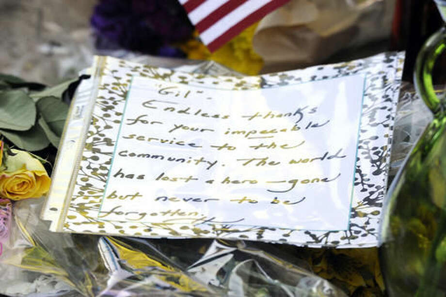 A note to peace officers is left at a shrine at the Palm Springs police station in Palm Springs, Calif., Sunday, Oct. 9, 2016, the day after multiple Palm Springs police officers were shot after a family disturbance Saturday. (AP Photo/Rodrigo Peña)