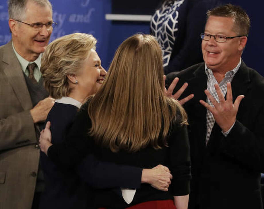 Democratic presidential nominee Hillary Clinton hugs her daughter Chelsea while speaking to town hall participants following the second presidential debate with Republican presidential nominee Donald Trump at Washington University in St. Louis, Sunday, Oct. 9, 2016. (AP Photo/John Locher)