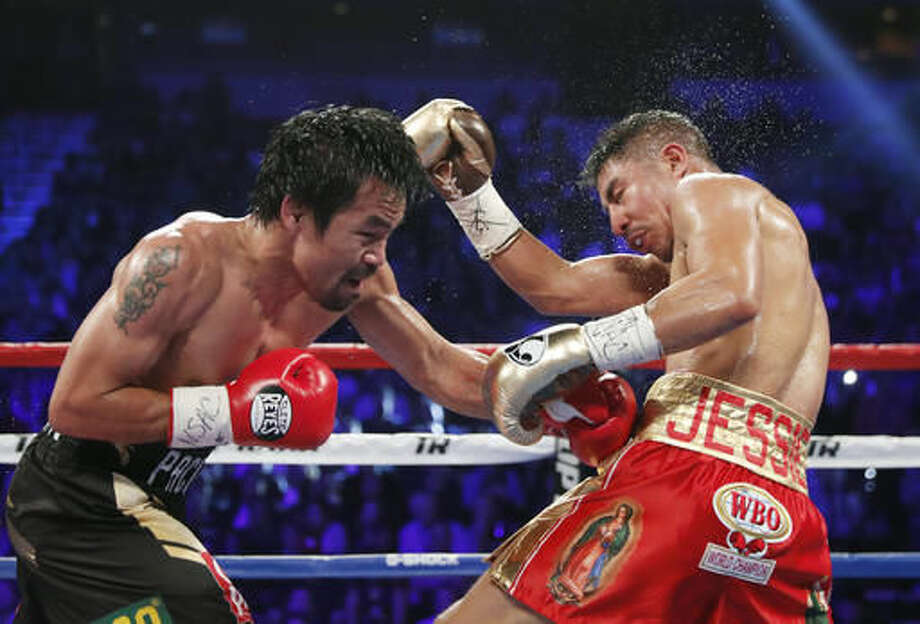 Manny Pacquiao, left, of the Philippines, hits Jessie Vargas during their WBO welterweight title boxing match, Saturday, Nov. 5, 2016, in Las Vegas. (AP Photo/Isaac Brekken)
