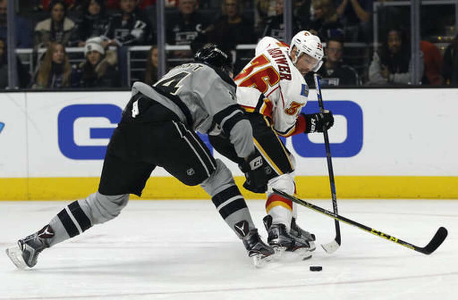 Calgary Flames right wing Troy Brouwer, right, centers a pass with Los Angeles Kings defenseman Derek Forbort, left, defending during the first period of an NHL hockey game in Los Angeles, Saturday, Nov. 5, 2016. (AP Photo/Alex Gallardo)