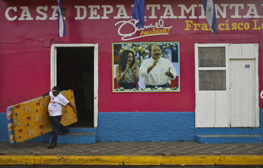 A man leaves the Sandinista National Front Party headquarters, in Masaya, Nicaragua, Saturday, Nov. 5, 2016. Nicaraguan President Daniel Ortega, pictured on the facade of the headquarters with his running mate and wife, Rosario Murillo, appears to have a clear path to a third consecutive term following recent moves that weakened the country's opposition. (AP Photo/Esteban Felix)