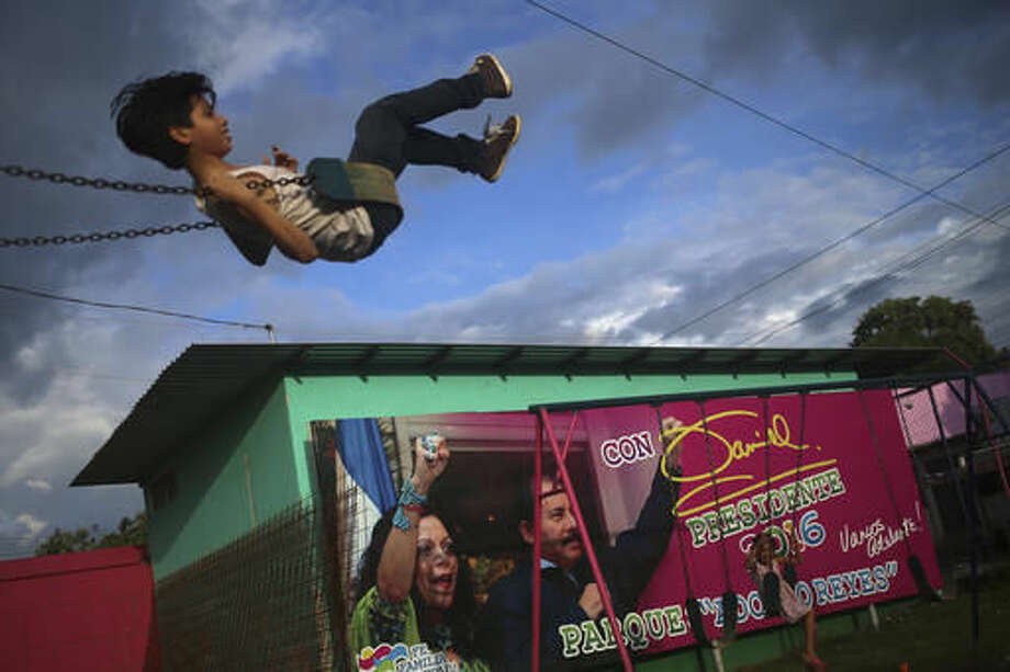 In this Friday, Nov. 4, 2016 photo, a boy swings in a park next to an election billboard promoting Nicaragua's President Daniel Ortega and running mate, his wife Rosario Murillo, in Managua, Nicaragua. Ortega appears to have a clear path to a third consecutive term following recent moves that weakened the country's opposition. Polls show the former guerrilla fighter easily winning with more than 50 percent of the vote. (AP Photo/Esteban Felix)