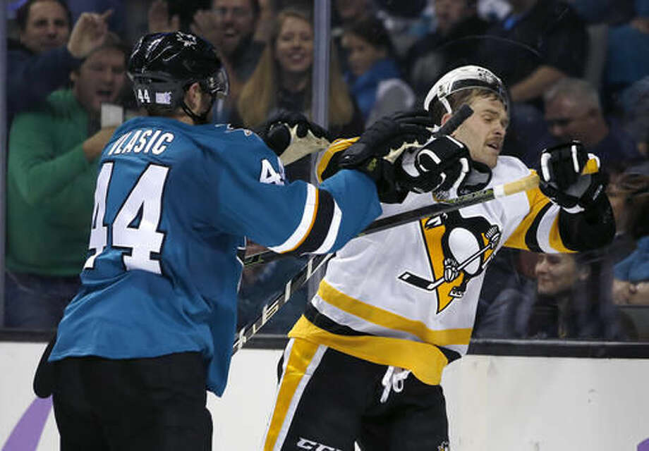 San Jose Sharks defenseman Marc-Edouard Vlasic (44) fights with Pittsburgh Penguins right wing Bryan Rust, right, during the second period of an NHL hockey game Saturday, Nov. 5, 2016, in San Jose, Calif. (AP Photo/Tony Avelar)