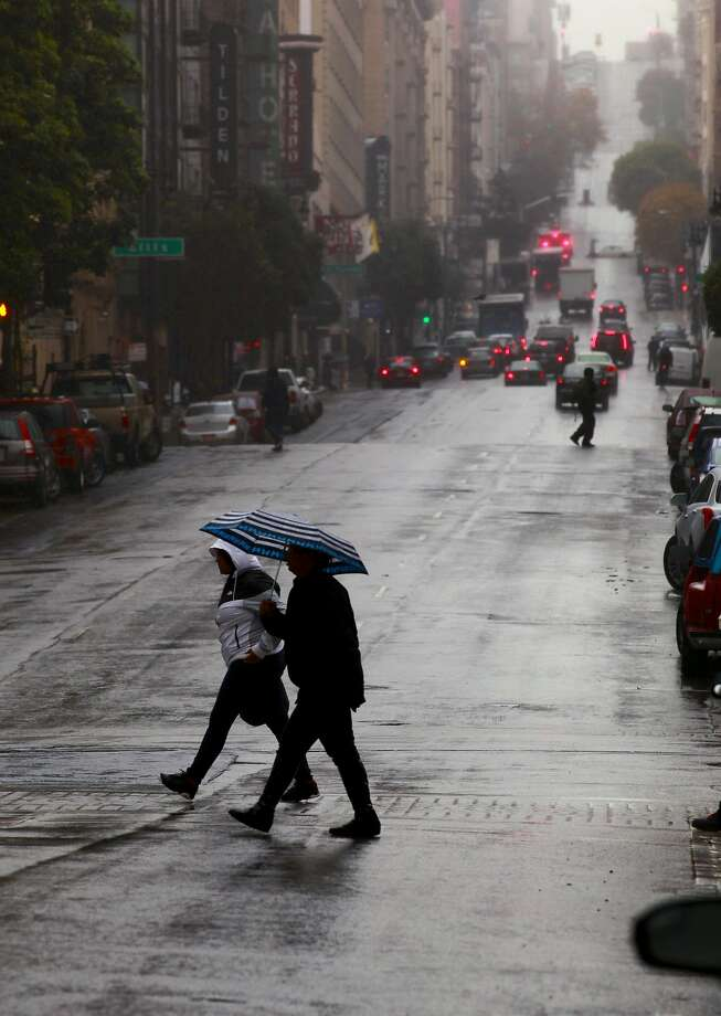 People shelter under umbrellas at Eddy and Taylor streets during a light rain across San Francisco on Nov. 30, 2016. Wednesday will be the coldest day of the week in the Bay Area as temperatures are expected to remain 50 degrees in San Francisco, 51 degrees in the East Bay and 55 degrees in the South Bay. Rain is expected to hit the San Francisco between mid-afternoon to 6 p.m. Wednesday, forecasters said. Photo: Michael Macor, The Chronicle