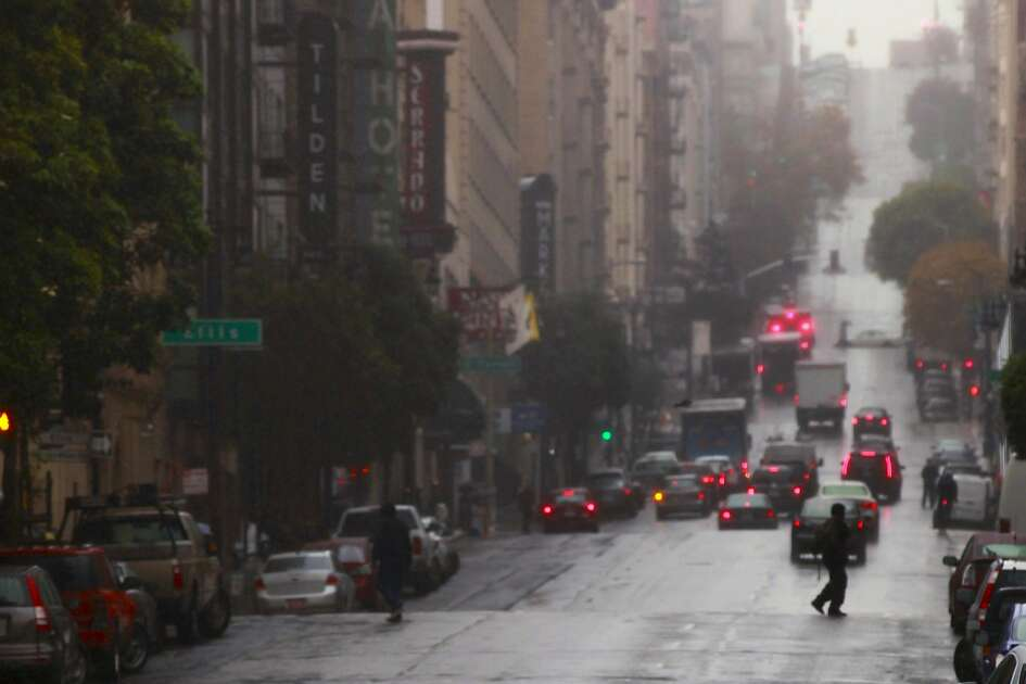 People shelter under umbrellas at Eddy and Taylor streets during a light rain across San Francisco, California, on Wednesday November 30, 2016.