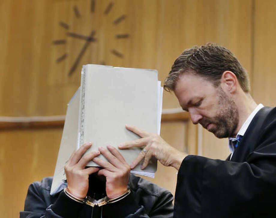 A 16-year-old South Korean covers his face in a court in Frankfurt, Germany, Monday, Oct. 10, 2016. He is accused of murder following the death a 41-year-old woman in an apparent exorcism ritual in a room in a Frankfurt hotel. At right his lawyer Thorsten Fuchs. (AP Photo/Michael Probst)