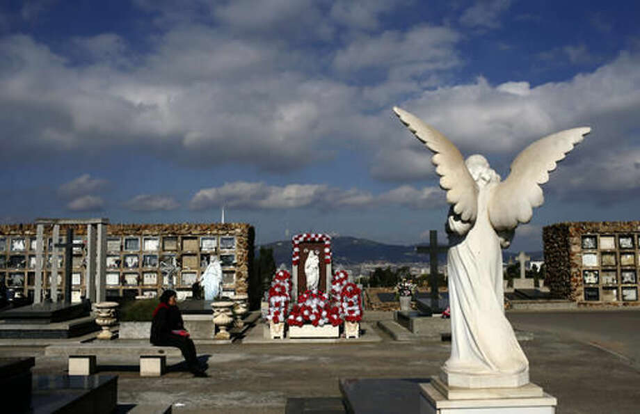A woman rests during All Saints Day, a Catholic holiday to reflect on the saints and deceased relatives, at the Montjuic cemetery in Barcelona, Spain, Tuesday, Nov. 1, 2016. (AP Photo/Manu Fernandez)