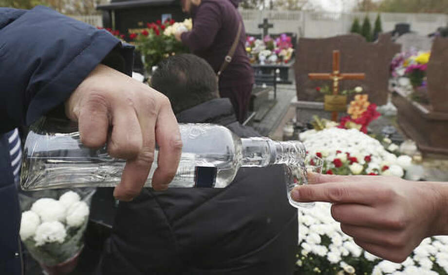 Members of the Roma community traditionally drink vodka on the graves of their passed relatives on All Saints' Day at the cemetery in Wlochy, Warsaw, Poland, Tuesday, Nov. 1, 2016.Candles illuminated tombstones in graveyards across Poland as people communed with the souls of the dead on Tuesday, All Saints' Day, observing one of the most sacred days in the calendar for this deeply Catholic nation. (AP Photo/Czarek Sokolowski)