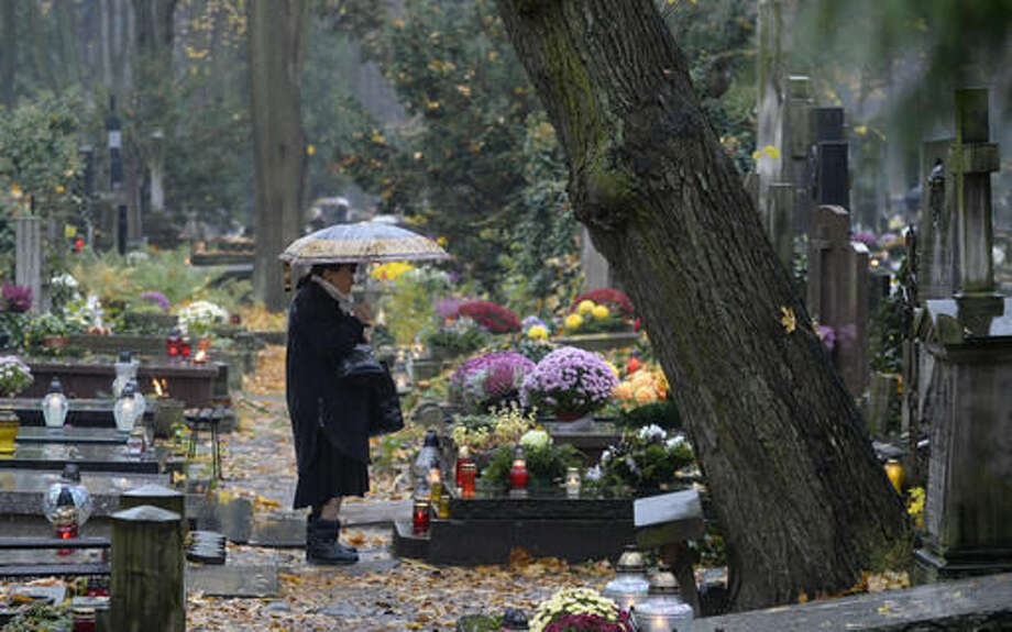 A woman stops in front of a grave at the Old Powazki cemetery in Warsaw, Poland, Tuesday, Nov. 1, 2016. Candles illuminated tombstones in graveyards across Poland as people communed with the souls of the dead on Tuesday, All Saints' Day, observing one of the most sacred days in the calendar for this deeply Catholic nation. (AP Photo/Alik Keplicz)