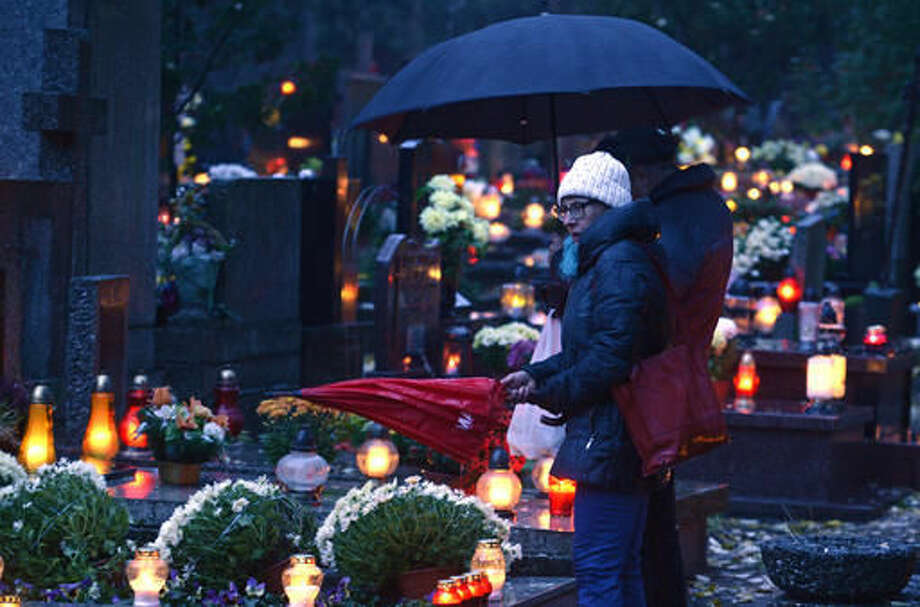 People light candles at the Powazki cemetery in Warsaw, Poland, Tuesday, Nov. 1, 2016. Candles illuminated tombstones in graveyards across Poland as people communed with the souls of the dead on Tuesday, All Saints' Day, observing one of the most sacred days in the calendar for this deeply Catholic nation. (AP Photo/Alik Keplicz)