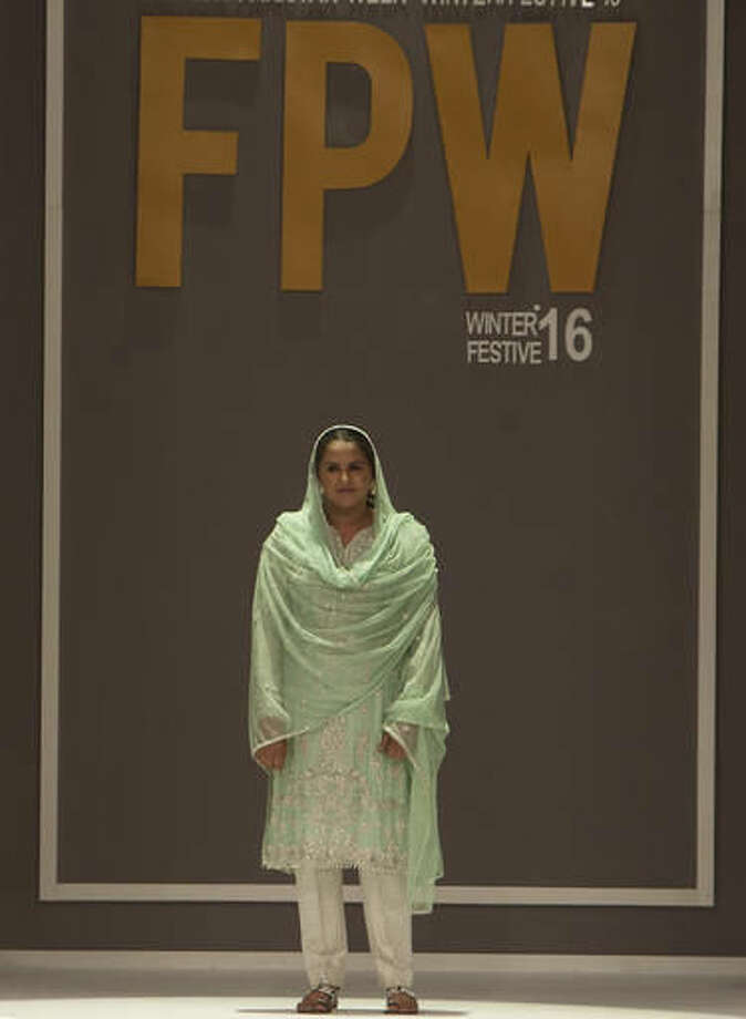 Pakistan's gang rape victim Mukhtar Mai walks on to stage during a fashion show in Karachi, Pakistan, Tuesday, Nov. 1, 2016. Gang-raped and paraded naked 14-years ago, Mukhtar Mai walked on during Pakistan fashion week on Tuesday. A red-carpet reception accorded in Pakistani southern city of Karachi by country's elite fashionista is her debut appearance, which she says she's doing as a symbol of courage for womenfolk. (AP Photo/Shakil Adil)