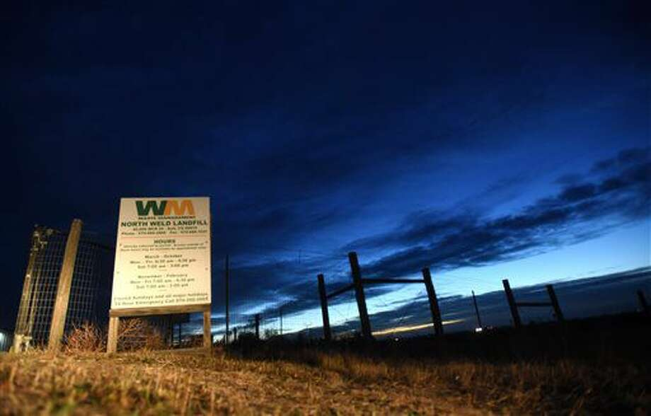 A sign is illuminated by a car as the sun begins to rise in the distance at the Waste Management landfill on Monday, Oct. 31, 2016 outside of Ault, Colo. Laramie County Sheriffs sent out a release saying they would begin the search at sunrise Monday. (Joshua Polson/The Greeley Tribune via AP)