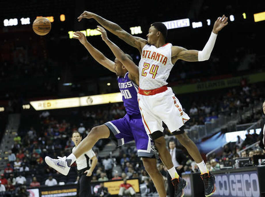Sacramento Kings' Arron Afflalo, left, passes the ball against the defense of Atlanta Hawks' Kent Bazemore, in the first quarter of an NBA basketball game in Atlanta, Monday, Oct. 31, 2016. (AP Photo/David Goldman)