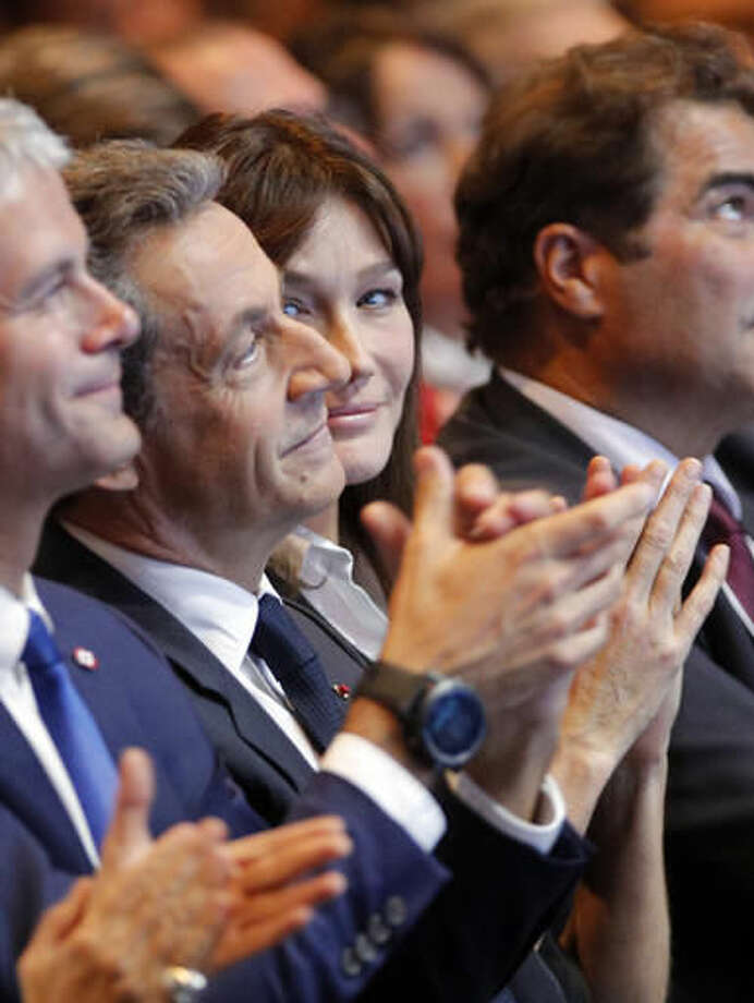 Carla Bruni-Sarkozy, center, looks at her husband, former French President Nicolas Sarkozy before his speech as he runs for the 2017 presidential election in Paris, France, Sunday, Oct. 9, 2016. (AP Photo/Christophe Ena)