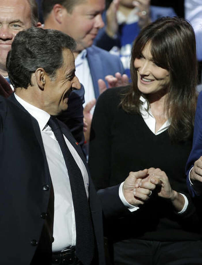 Former French President Nicolas Sarkozy, holds the hand of his wife Carla Bruni-Sarkozy, at the end of his speech as he runs for the 2017 presidential election in Paris, France, Sunday, Oct. 9, 2016. (AP Photo/Christophe Ena)