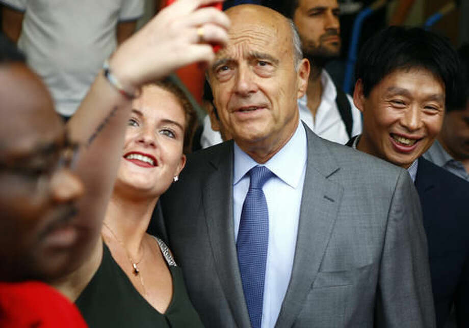 FILE - In this Sept. 8, 2016 file photo, Alain Juppe, former French Prime Minister and mayor of Bordeaux, has a selfie taken with onlookers as he visits the Chinese Fashion Center at Aubervilliers, in the outskirts of Paris. The rivalry is heating up between the two top contenders for France's conservative presidential primary next month, with the reassuring Alain Juppe and the brash Nicolas Sarkozy dueling over their visions of France's national identity, immigration and Islam (AP Photo/Francois Mori, File)