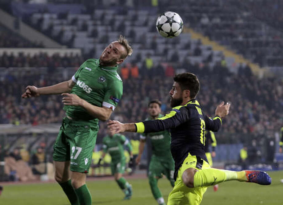 Ludogorets player Cosmin Moti, left, battles for the ball Arsenal's Olivier Giroud during the Champions League group A soccer match at Vassil Levski stadium in Sofia, Bulgaria, Tuesday, Nov. 1, 2016. (AP Photo/Valentina Petrova)