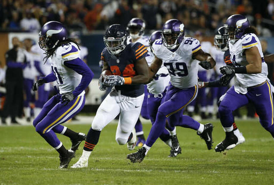 Chicago Bears running back Jordan Howard (24) runs from Minnesota Vikings strong safety Anthony Harris, from left, Danielle Hunter (99) and Eric Kendricks (54) during the first half of an NFL football game in Chicago, Monday, Oct. 31, 2016. (AP Photo/Nam Y. Huh)