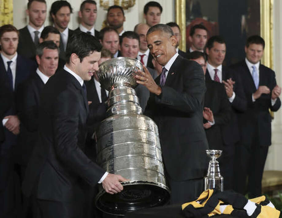 President Barack Obama helps Pittsburgh Penguins team captain Sidney Crosby carry the Stanley Cup during a ceremony honoring the Stanley Cup champion Pittsburgh Penguins, Thursday, Oct. 6, 2016, during a ceremony in the East Room of the White House in Washington. (AP Photo/Manuel Balce Ceneta)