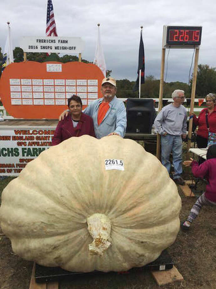In this Oct. 8, 2016 photo provided by Ron Wallace, Richard and Catherine Wallace stand with a 2,261.5-pound pumpkin that Richard grew to set the North American giant pumpkin record at the Frerichs Farm Pumpkin Weigh Off in Warren, R.I. WJAR-TV reported Richard Wallace's pumpkin beat the record set by his son, Ron, at the same event last year. (Ron Wallace via AP)