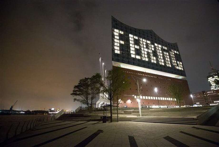 In this Oct. 31, 2016 photo the word 'Fertig' (lit. 'Done') can be seen on the facade via lights in specific windows of the Elbphilharmonie in Hamburg, Germany. The construction of the Elbphilharmonie in Hamburg is completed - roughly nine years after the laying of the foundation stone. (Christian Charisius/dpa via AP)