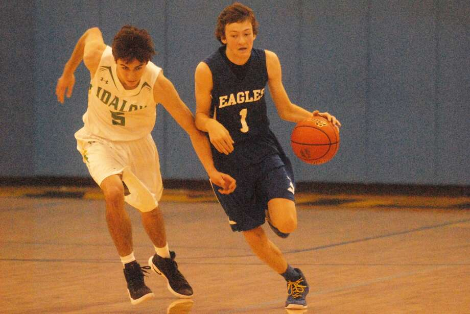 Plainview Christian Academy's Todd Earhart, 1, dribbles against Idalou's Mark Caballero, 5, during a game at the Nazareth Tournament Thursday. Earhart scored 27 points in two games, including 20 against Bovina, but the Eagles lost both contests. Photo: Skip Leon/Plainview Herald