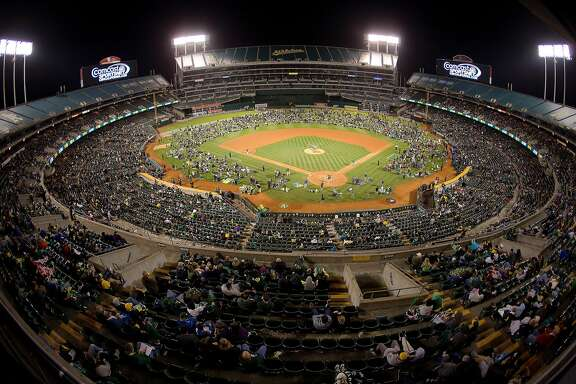 OAKLAND, CA - JUNE 19:  Fans crowd onto the field for fireworks after a game between the Oakland Athletics and the Los Angeles Angels of Anaheim at O.co Coliseum on June 19, 2015 in Oakland, California.  The Angels won 12-7.  (Photo by Brian Bahr/Getty Images)