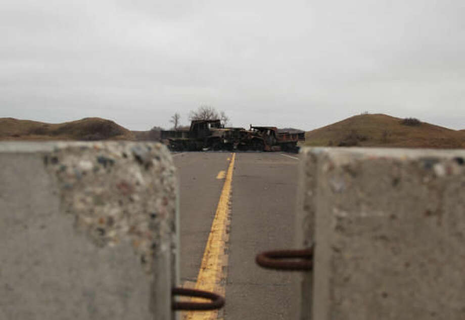 Burned out trucks blocks a causeway on Highway 1806, seen from the police side of a barricade of a protest camp in Cannon Ball, N.D., Sunday, Oct. 30, 2016. Demonstrators have been camping for months in an effort to block the nearly 1,200-mile, four-state pipeline. (AP Photo/John L. Mone)