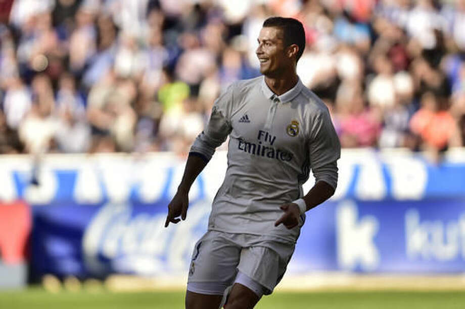 Real Madrid's Cristiano Ronaldo, left, smiles after scoring his second goal during the Spanish La Liga soccer match between Real Madrid and Deportivo Alaves, at Mendizorroza stadium, in Vitoria, northern Spain, Saturday, Oct. 29, 2016. (AP Photo/Alvaro Barrientos)