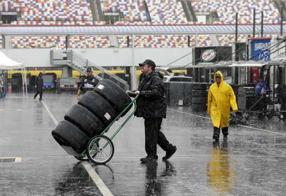 FILE - In this Oct. 7, 2016, file photo, a crew member hauls tires through the NASCAR Xfinity garage in the rain at Charlotte Motor Speedway in Charlotte, N.C. NASCAR did the best it possibly could after a nearly washed-out weekend in Charlotte. (AP Photo/Chuck Burton, File)