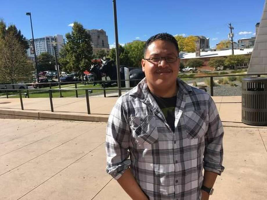 """Tito Marcos, a system administrator for a Denver firm, stands outside the Denver Art Museum during his lunch break on Monday, Oct. 10, 2016. A registered independent, Marcos says he is tired of the drama of a presidential campaign, which he compared to """"a heavyweight wrestling match."""" He's leaning toward voting for a third-party candidate. (AP Photo/Jim Anderson)"""