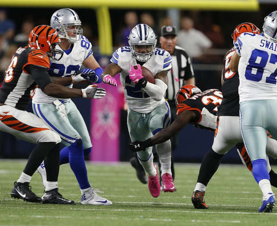Dallas Cowboys running back Ezekiel Elliott (21) runs through Cincinnati Bengals Shawn Williams, right, in the second half of an NFL football game, Sunday, Oct. 9, 2016, in Arlington, Texas. (Jose Yau/Waco Tribune Herald, via AP)