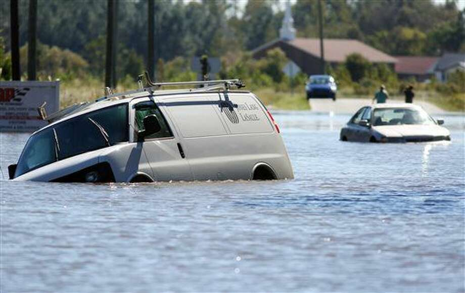 Several abandoned vehicles sit in flood waters at the intersection of John and Benton Streets Monday, Oct. 10, 2016, in Goldsboro, N.C. that are expected to rise through Tuesday morning. (Casey Mozingo/The Goldsboro News-Argus via AP)