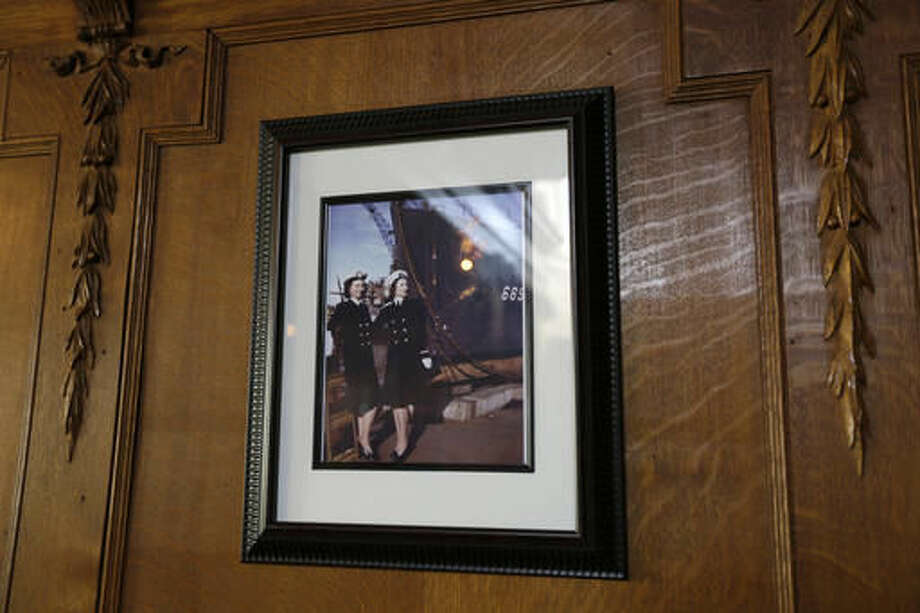 In this photo taken Friday, Oct. 7, 2016, a historic photograph of a pair of women Naval officers hangs on a wall at the Vino Godfather winery on Mare Island in Vallejo, Calif. Mare Island was the site of the first Naval Yard on the Pacific Coast. Long before San Francisco was a tech capital or hippie haven, it was a military town, and some of the region's wineries are located in the footprints of what were once military bases. (AP Photo/Eric Risberg)