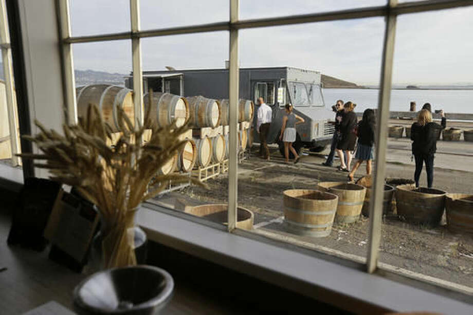 In this photo taken Friday, Oct. 7, 2016, people make their way toward a food truck and look at the view of San Francisco Bay outside the Riggers Loft Wine Company in Richmond, Calif. The winery is located in an historic building that once played a vital role in building the Liberty and Victory ships of World War II. Long before San Francisco was a tech capital or hippie haven, it was a military town, and some of the region's wineries are located in the footprints of what were once military bases. (AP Photo/Eric Risberg)