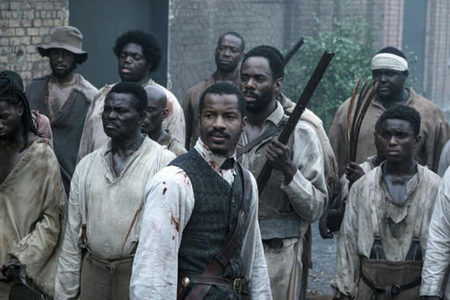 """FILE - In this file image released by Fox Searchlight Films shows Nate Parker as Nat Turner, center, in a scene from """"The Birth of a Nation."""" Nate Parker's Nat Turner biopic """"The Birth of a Nation,"""" opened with a disappointing $7.1 million, according to studio estimates Sunday, Oct. 9, 2016. (Jahi Chikwendiu/Fox Searchlight via AP, File)"""