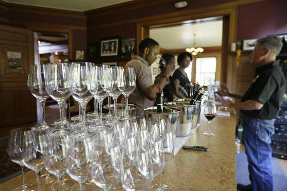 In this photo taken Friday, Oct. 7, 2016, people taste wine at the Vino Godfather winery on Mare Island in Vallejo, Calif. Mare Island was the site of the first Naval Yard on the Pacific Coast. Long before San Francisco was a tech capital or hippie haven, it was a military town, and some of the region's wineries are located in the footprints of what were once military bases. (AP Photo/Eric Risberg)