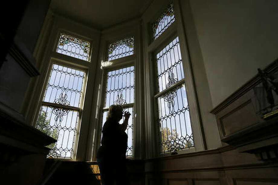 In this photo taken Friday, Oct. 7, 2016, a woman tastes wine near a stained-glass window on a stairway at the Vino Godfather winery on Mare Island in Vallejo, Calif. Mare Island was the site of the first Naval Yard on the Pacific Coast. Long before San Francisco was a tech capital or hippie haven, it was a military town, and some of the region's wineries are located in the footprints of what were once military bases. (AP Photo/Eric Risberg)