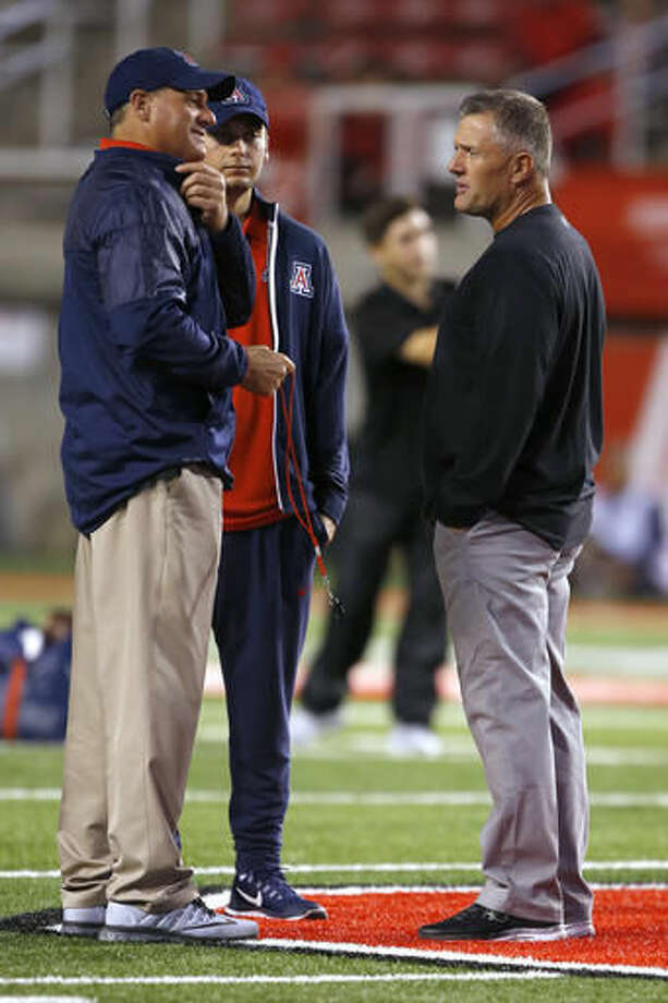 Arizona coach Rich Rodriguez, left, talks with Utah coach Kyle Whittingham, right, before an NCAA college football game, Saturday, Oct. 8, 2016, in Salt Lake City. (AP Photo/George Frey)p