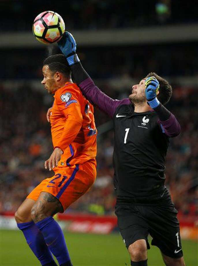Netherlands' Memphis Depay, left, goes for a header while France's goalkeeper Hugo Lloris tries to divert the ball during the World Cup Group A qualifying soccer match in the ArenA stadium in Amsterdam, Netherlands, Monday, Oct. 10, 2016. (AP Photo/Peter Dejong)